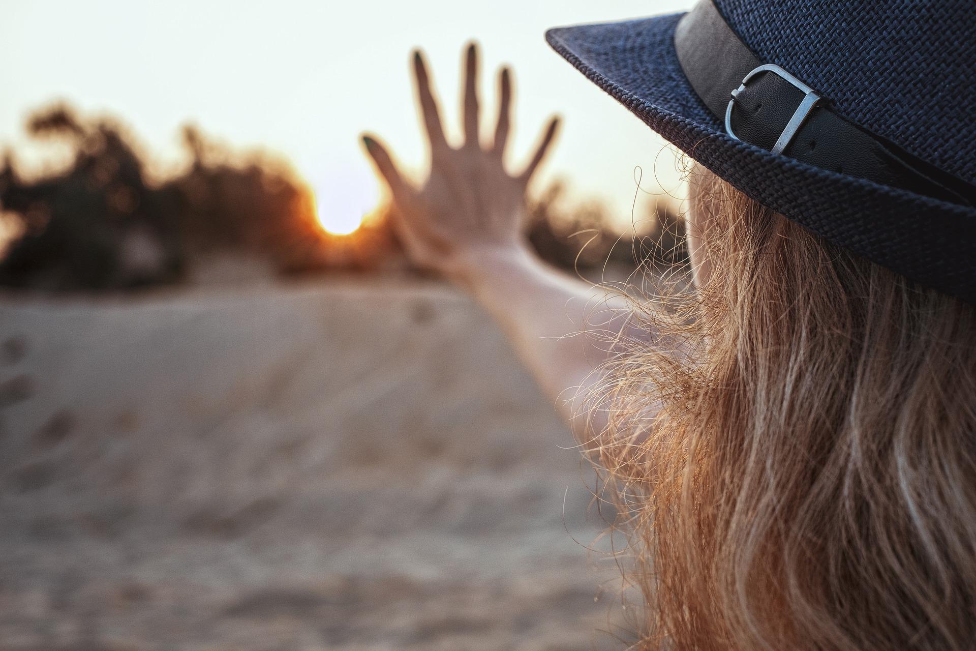 Frau mit Hut und Hand vor Sonnenaufgang